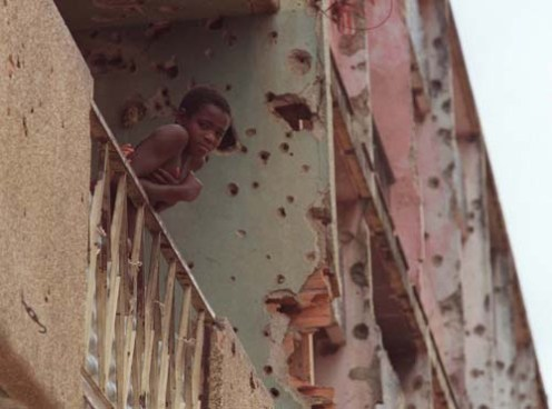 A young child leans over the balcony of his flat in the central Angolan town of Huambo, Wednesday 18 Febraury, 1998, on a street that marked the front-line of a 55 day battle between government and rebel UNITA forces in 1993.(AP Photo/Adil Bradlow)